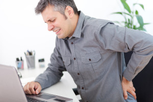 Image of a young man having a back pain while sitting at the working desk
